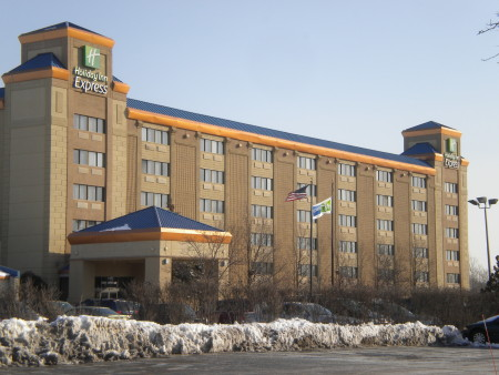 A photo of a Holiday Inn hotel and parking area on a sunny day.