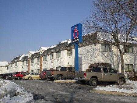 A photo of a Motel 6 hotel building and parking area.