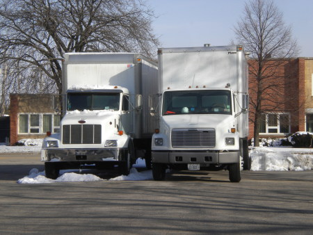 A photo of 2 straight trucks parked in a parking lot.